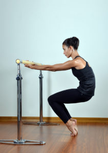 Dancer stretching at the barre in a dance studio.